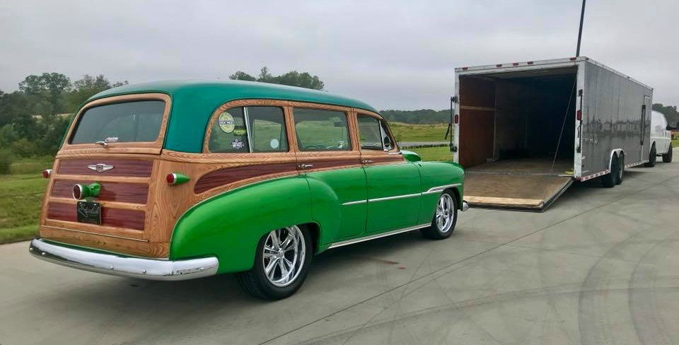 Green woody about to enter enclosed shipping trailer.