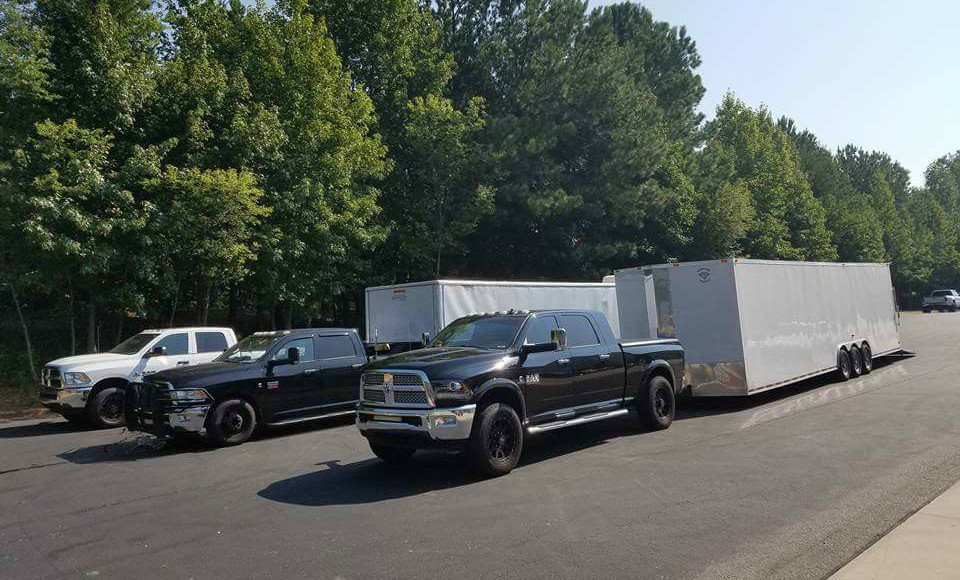 Three trucks with enclosed trailers parked in a row.